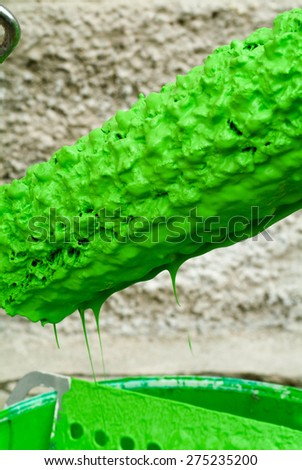 Green paint can and paint roller - stock photo