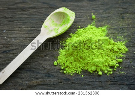green paint powder on wooden table - stock photo