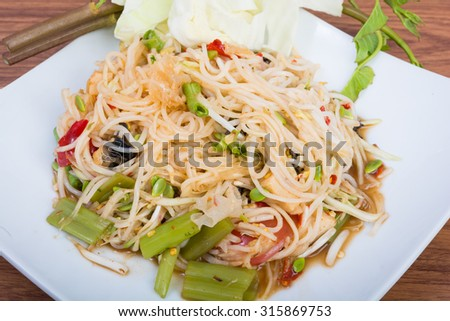 green papaya spicy salad Thai style on wooden background