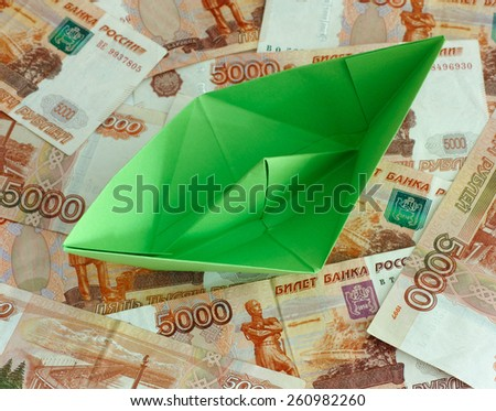 Green paper boat on five thousand rubles banknotes. Close up.