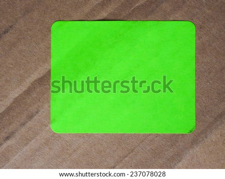 Green paper tag label sticker over brown corrugated cardboard box - stock photo