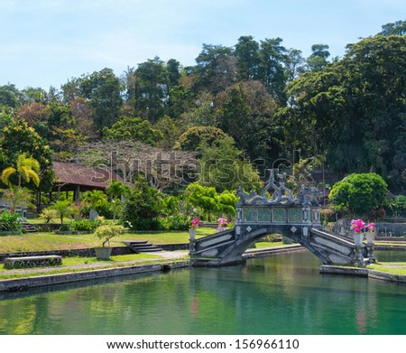 Green park with clean lake and stone balinese style arch bridge, Tirtaganga, Bali