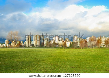 Green park with skyscrapers on the background. Vancouver, Canada - stock photo