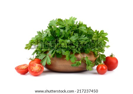 Green parsley in bamboo plate and cherry tomatoes on white background - stock photo
