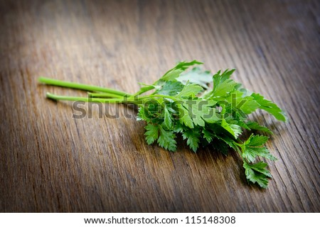 Green parsley lying on a dark brown table. - stock photo
