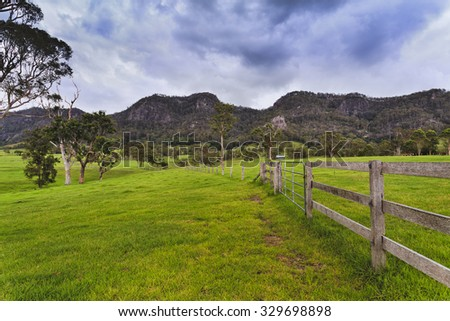 Green pasture field of a farm in rural NSW in Australia - agricultural site for steer growth with fences and mountain range in background - stock photo