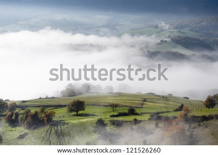 green pasture with trees and shrubs, on a cold morning with fog in the valley - stock photo