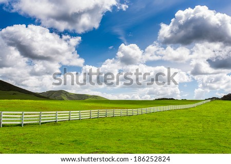 Green Pasture With White Fence With Large Puffy Clouds - stock photo