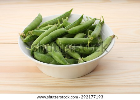 Green  pea pods in white dish  on wooden table,closeup