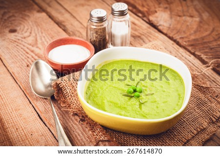 Green pea soup in a bowl with bread and sour cream on line tablecloth - stock photo