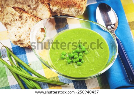 Green pea soup in a transparent bowl on a colorful tablecloth.