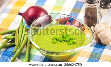 Green pea soup in a transparent bowl on a colorful tablecloth. - stock photo