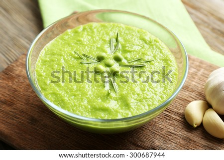 Green pea soup in glass bowl on wooden cutting board, closeup