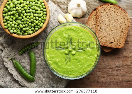 Green pea soup in glass bowl on wooden cutting board with sackcloth, top view - stock photo