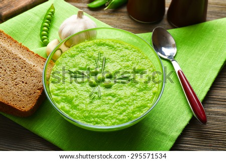 Green pea soup in glass bowl on wooden table with napkin, closeup - stock photo