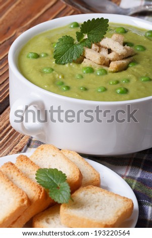 Green pea soup with croutons closeup. vertical