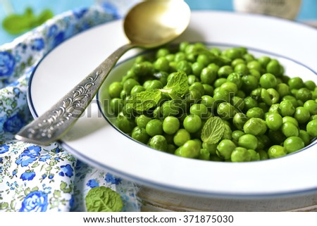 Green pea with mint in rustic style. - stock photo