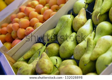 green pear and apricot fruits in a supermarket