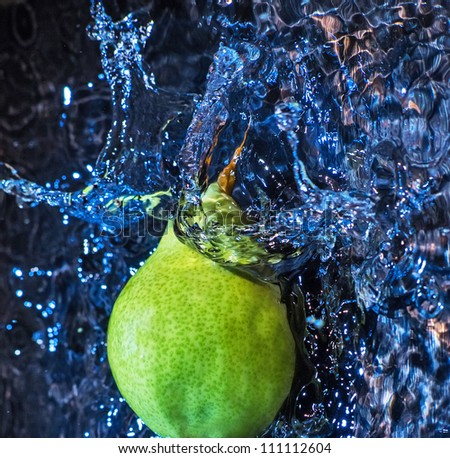 green pear dropped in water. Studio shot