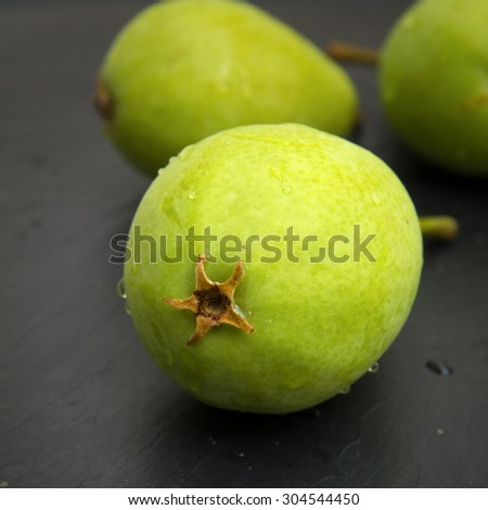green pears on black slate surface