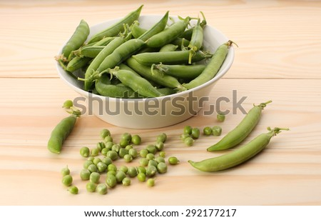 Green peas  and pea pods in white dish on wooden table,closeup