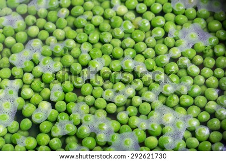 Green peas being boiled in a pot - stock photo