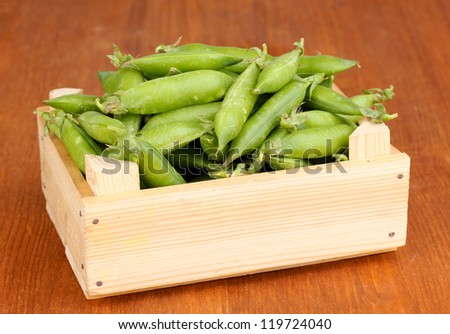 Green peas in crate on wooden background