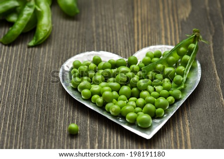 Green peas in metal vintage bowl on dark wooden background - stock photo