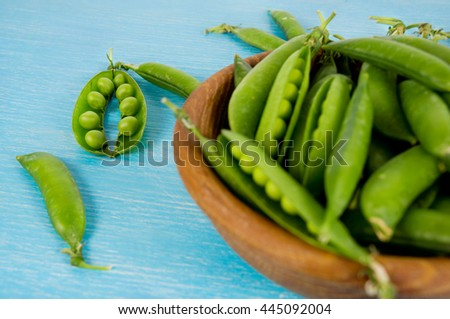 Green peas in wooden bowl on wooden background. Fresh pea pods. Young and sweet peas on vintage background. Heap of green pea pods on wooden table. - stock photo