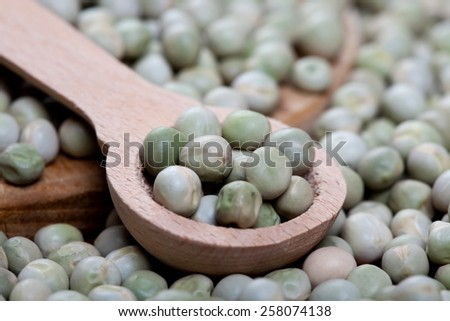green peas on a old wooden spoon, closeup - stock photo