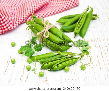 green peas with leaf on a old wooden background - stock photo
