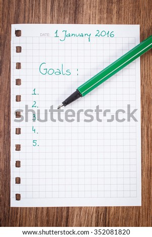 Green pen and notebook for writing resolutions and goals for new year - stock photo