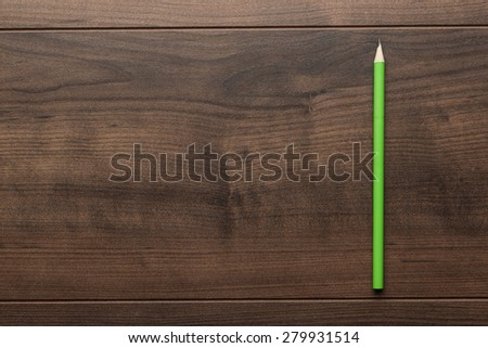 green pencil on the brown wooden table - stock photo