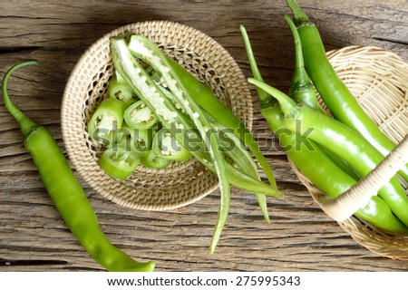 green pepper in wicker basket on wooden background