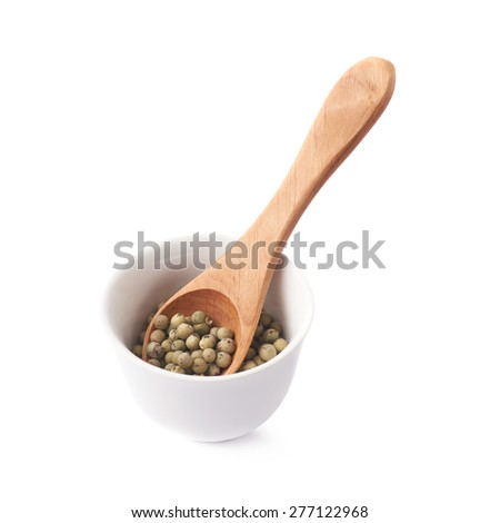 Green peppercorn with the wooden spoon in a white ceramic cup isolated over the white background