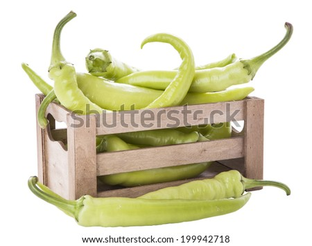 green peppers in a wooden crate isolated on white background