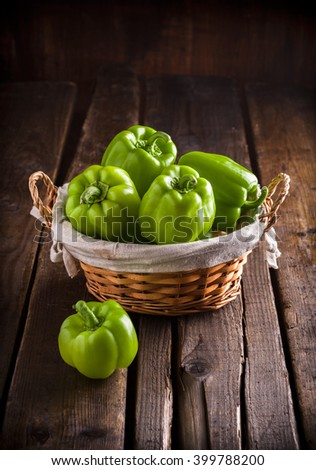 Green peppers in rustic wicker basket on rustic wooden table - stock photo