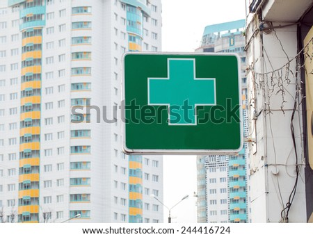 Green pharmacy sign on the background of houses. - stock photo