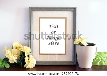 Green picture frame sitting on a wood shelf with flowers and a mug sitting next to it. Empty space in the photo frame canvas for adding your text or images. - stock photo