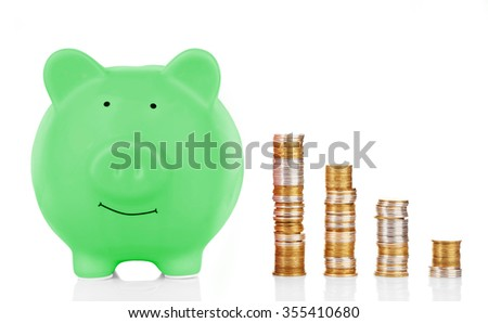 Green piggy bank with coins isolated on white - stock photo