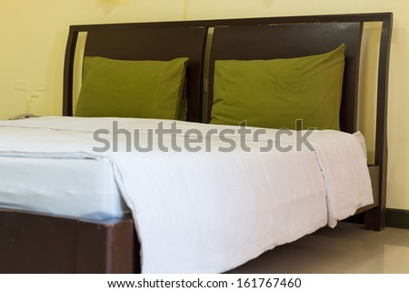 Green pillows on white clean bed - stock photo