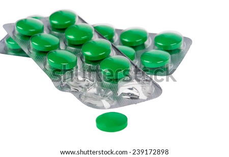 Green pills and blisters on white background - stock photo