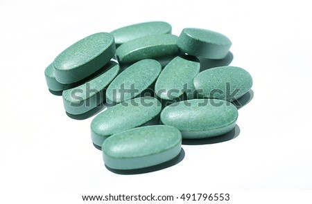 Green pills on a white background