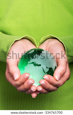 Green planet Earth in woman hand - stock photo
