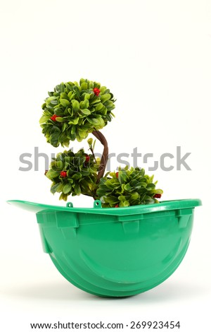 Green plant in green  helmet on white - environmental friendly industry concept - stock photo