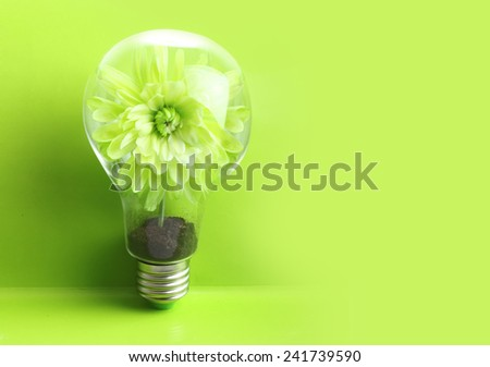 Green plant in soil inside light bulb on green background. Eco concept. - stock photo