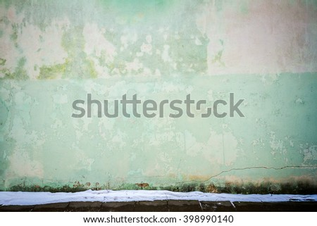 Green plaster street wall and ground covered with snow - stock photo