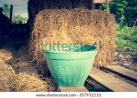 Green Plastic Basket With Hay Stack Background - stock photo