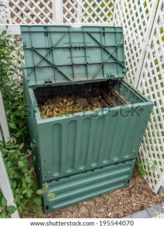 Green plastic compost bin full of organic and domestic food scraps - stock photo
