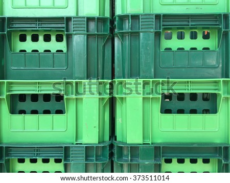 Green Plastic crates stacked packing containers background on front view . - stock photo